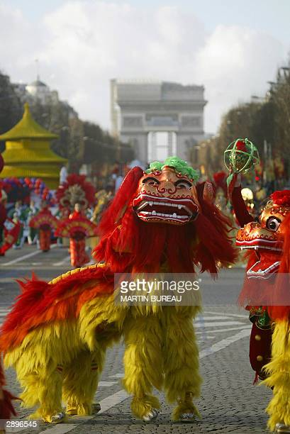 Participants dance in a traditional dragonanddrums Chinese new year parade on the Champs Elysees in Paris 24 January 2004 to celebrate the start of...
