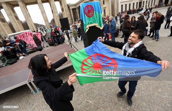 Participants dance with a Romani flag at a proRomani demonstration in front of the Brandenburg Gate on International Romani Day on April 8 2015 in...