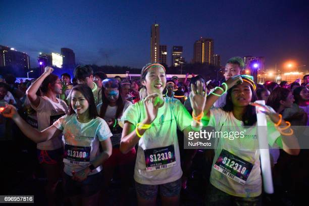 Participants dance with music during the Skechers Blacklight Run Thailand at Makkasan Airport Rail Link Station in Bangkok Thailand on 17 June 2017...