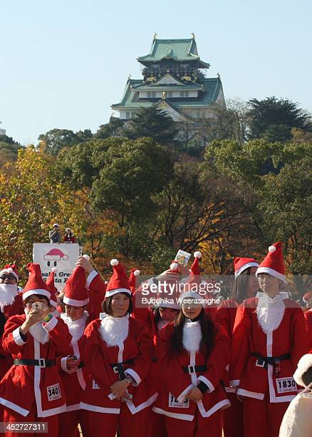 Participants dressed as Santa Claus get ready to jog before the 5th annual Osaka Great Santas run at fornt of the Osaka Castle on December 1 2013 in...