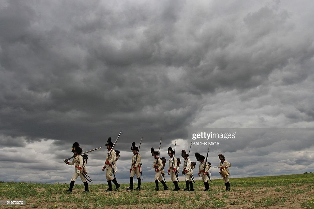 Participants dressed as soldiers of the Austrian Empire fire their guns on July 10, 2014 as they take part in the reenactment of the historic Napoleonic march from Seefeld-Kadolz, Austria to Dobsice, Czech Republic. During two days amateur actors march the 20km long distance to commemorate the 1809 Battle of Znojmo.
