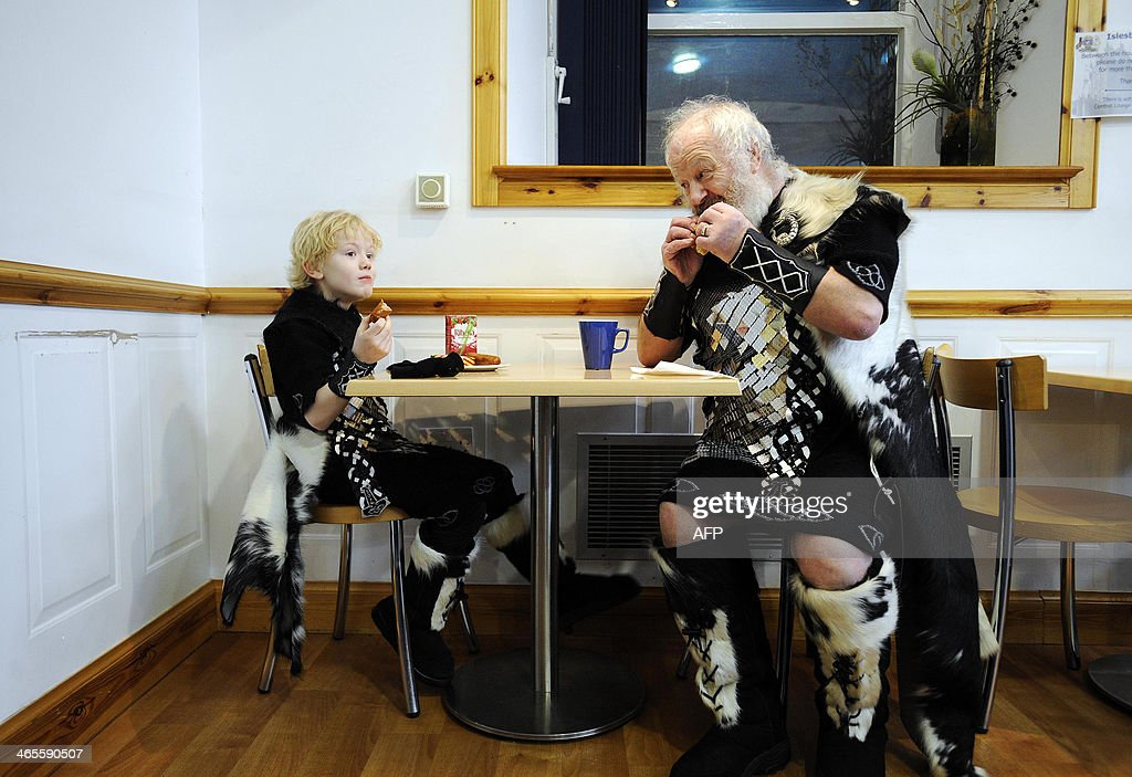 Participants dressed as Vikings eat breakfast as they prepare to participate in the annual Up Helly Aa festival in Lerwick Shetland Islands on...
