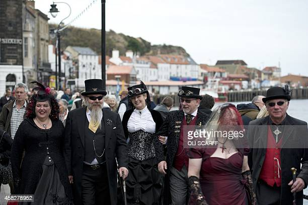 Participants dressed in gothic costumes walk through the streets of Whitby Northern England on November 2 as they attend the biannual 'Whitby Goth...