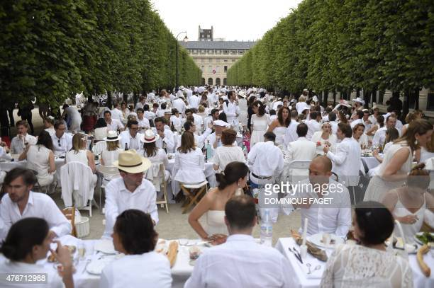 Participants dressed in white enjoy their meal during a 'Diner en Blanc' at the gardens of the PalaisRoyal in Paris on June 11 2015 The 'Diner en...