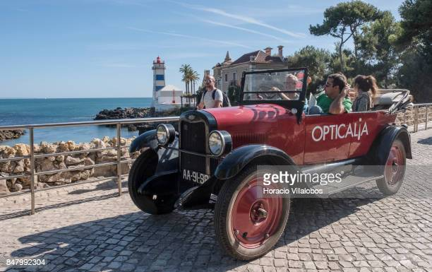 Participants drive a classic Chevrolet on Rei Humberto II de Italia Avenue in front of Santa Marta Lighthouse during Cascais Classic Motor Show on...