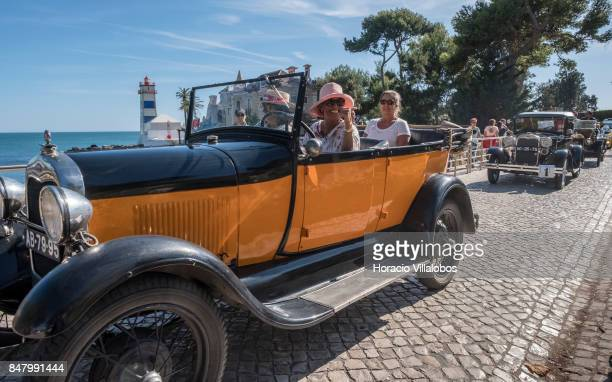 Participants drive a classic Ford followed by other classic cars on Rei Humberto II de Italia Avenue in front of Santa Marta Lighthouse during...