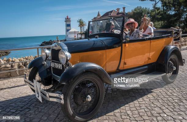 Participants drive a classic Ford on Rei Humberto II de Italia Avenue in front of Santa Marta Lighthouse during Cascais Classic Motor Show on...