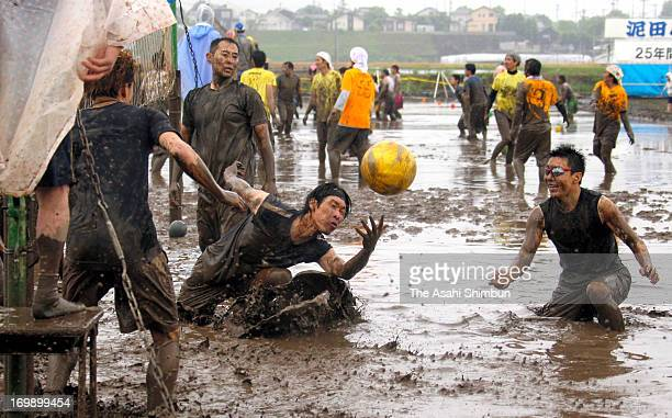 Participants enjoy playing volleyball in a mud paddy on June 2 2013 in Nakatsu Oita Japan The paddy volleyball has been held since 1989 as the...