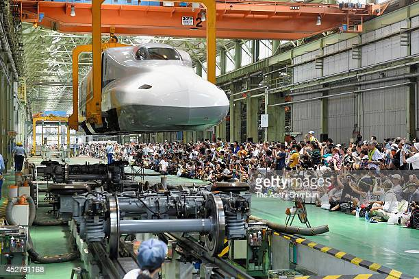 Participants enjoy the 'Doctor Yellow' train tour at JR Tokai Hamamtsu factory on July 26 2014 in Hamamatsu Shizuoka Japan The bright yellow train...
