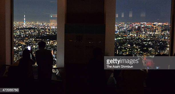 Participants enjoy the Tokyo nightscape during the overnight staying event at the observation deck of the Sunshine 60 building on May 2 2015 in Tokyo...