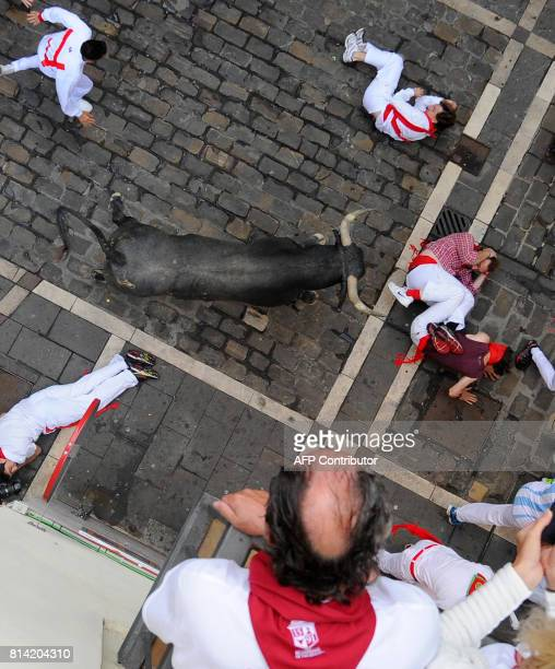 Participants fall past a Miura's fighting bull during the eighth and last bull run of the San Fermin festival in Pamplona northern Spain on July 14...