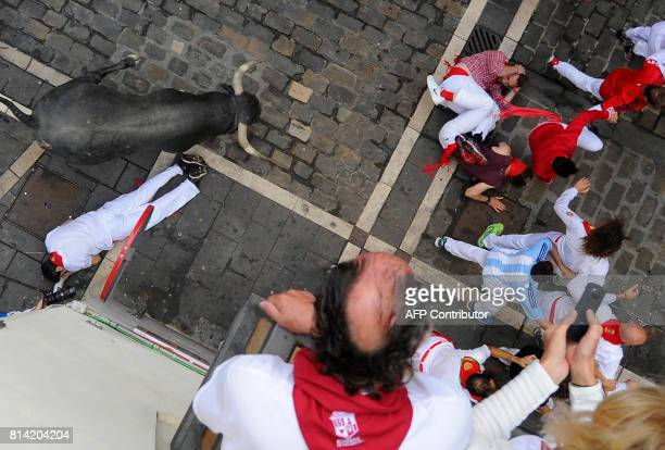Participants falls as others run ahead of a Miura's fighting bull during the eighth and last bull run of the San Fermin festival in Pamplona northern...