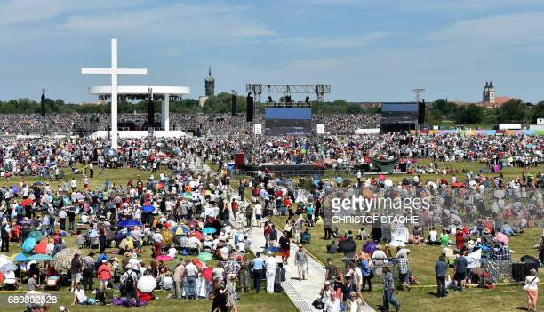 Participants follow the final mass of the Kirchentag festival celebrating the 500th anniversary of the Reformation at a meadow near the river Elbe...