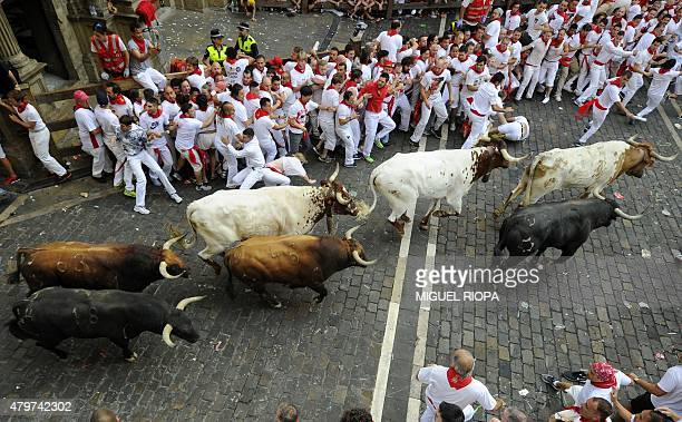Participants gather as Jandilla bulls run past during the fist 'encierro' of the San Fermin Festival in Pamplona northern Spain on July 7 2015 The...