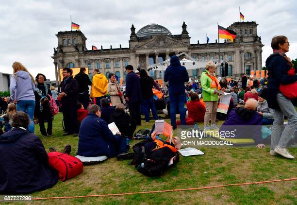 Participants gather in front of the Reichstag building that houses Germany's Bundestag lower house of parliament in Berlin on May 24 2017 ahead of...