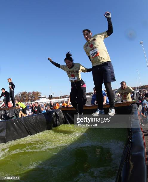 Participants go through the Artic Enema obstacle during the Tough Mudder event at Raceway Park on October 21 2012 in Englishtown New Jersey