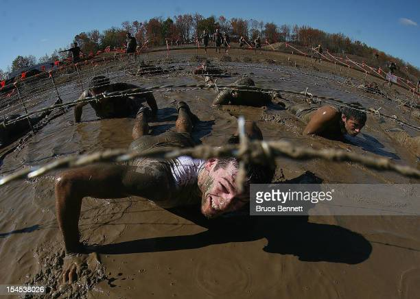 Participants go through the Kiss of Mud obstacle at the Tough Mudder event at Raceway Park on October 21 2012 in Englishtown New Jersey