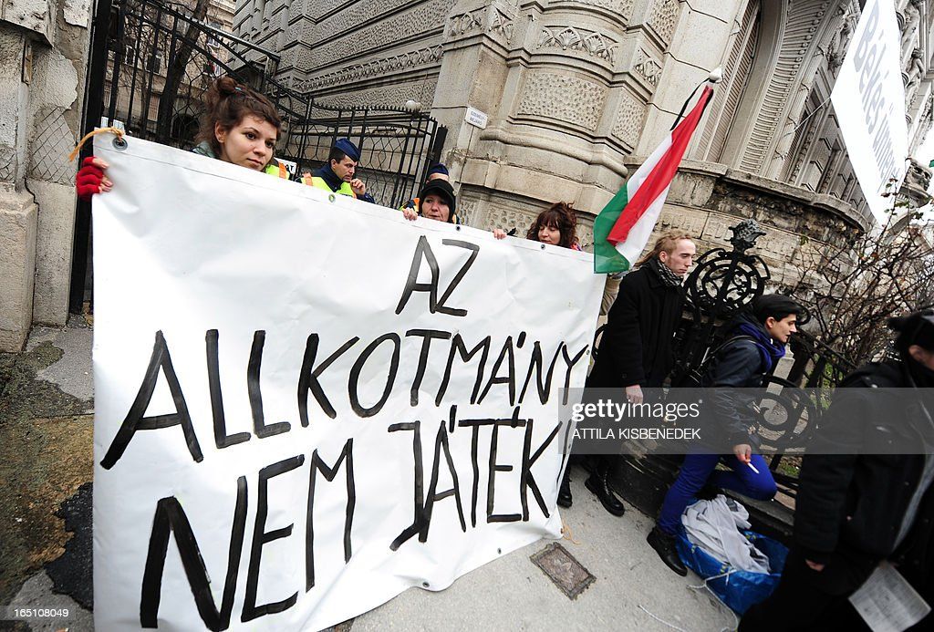 Participants hold a banner reading 'The constitution isn't a game' - to protest against the new Hungarian Constitution during an anti-government demonstration in front of the headquarter of the governor FIDESZ in Budapest on March 30, 2013. The fourth modification of the basic law will be come into force on April 1.