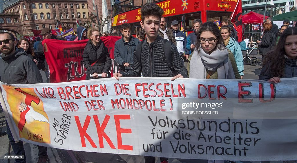 Participants hold a banner reading 'We break the bonds of the EU and the monopolies' during a May Day or International Workers' Day rally in Frankfurt am Main, central Germany, on May 1, 2016. / AFP / dpa / Boris Roessler / Germany OUT