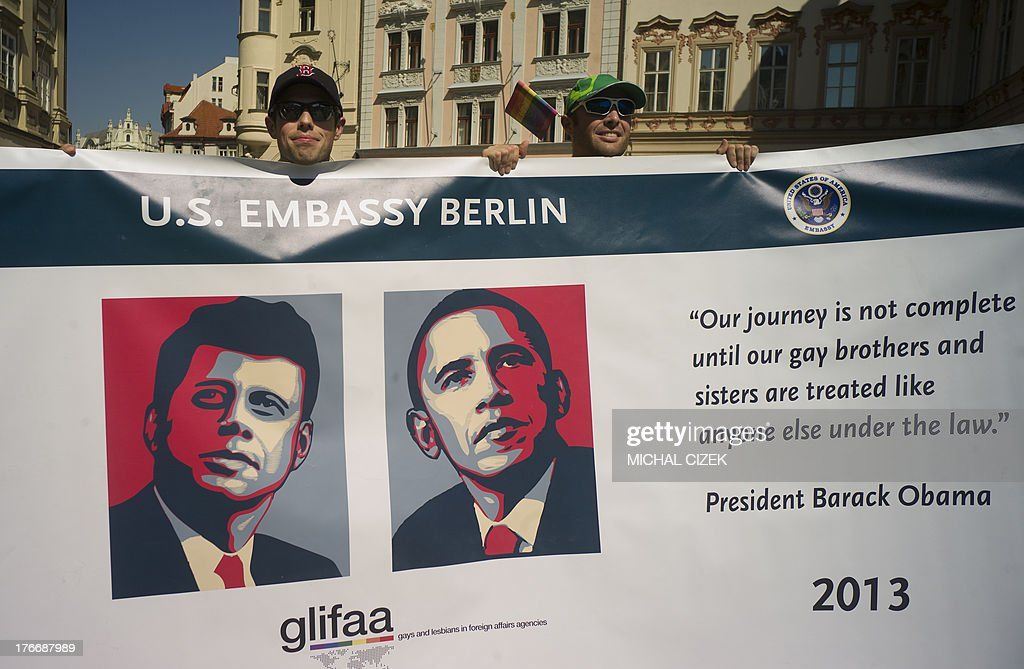 Participants hold a banner with the portraits of US Presidents John F Kennedy (L) and Barack Obama during the third gay pride festival in the Czech capital Prague on August 17, 2013. AFP PHOTO / MICHAL CIZEK
