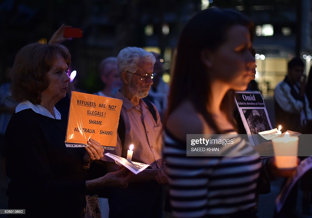 Participants hold a candle light vigil for an Iranian refugee, who died after setting himself on fire, in Sydney on April 30, 2016. The 23-year-old known as Omid set fire to himself on April 27, 2016 on the remote Pacific island where he had been sent by Australia, which refuses to resettle boat people even if found to be genuine refugees. / AFP / SAEED