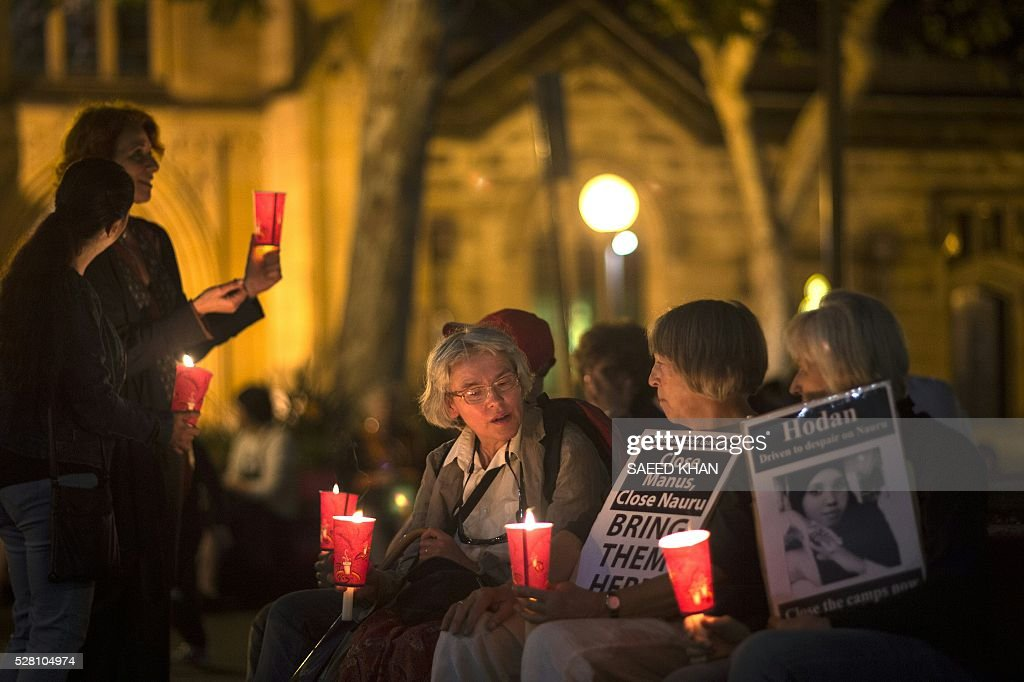 Participants hold a candle light vigil for two refugees, a Somali woman and an Iranian man who set themselves on fire on the remote Pacific island of Nauru, in Sydney on April 30, 2016. More than 750 asylum-seekers held in a Papua New Guinea detention camp launched legal action on May 4, 2016 to be moved to Australia after a court in the Pacific nation found the centre unconstitutional. / AFP / SAEED