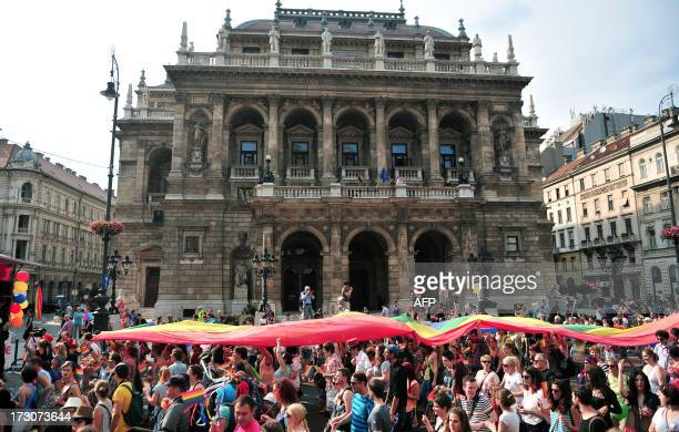 Participants hold a rainbowflag during a gay pride march in front of the State Opera House in Budapest Hungary on July 6 2013 AFP PHOTO / STR HUNGARY...