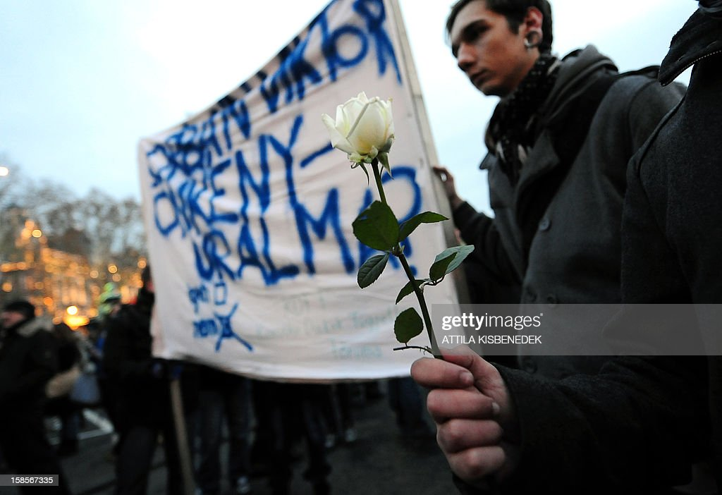 Participants hold a rose in front of a placard, 'Autocracy of autocracyiktor Orban (Hungarian premier) NO' as around 1,000 protesters -- including pupils from over 40 schools, according to organisers -- preapare for their march on December 19, 2012 through downtown Budapest. Protests over higher education reform in Hungary spread further Wednesday, even after the government made apparent concessions to students, angry about planned tuition fees and commitments to work in Hungary. Many wore roses to symbolise what they call the 'Student Winter Rose revolution.'