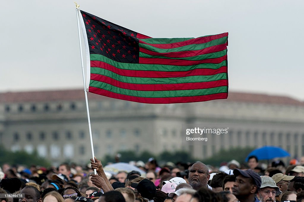 Participants hold a U.S. flag while gathered at the National Mall in Washington, D.C., U.S., on Wednesday, Aug. 28, 2013. U.S. President Barack Obama, speaking from the same Washington stage where Martin Luther King Jr. delivered a defining speech of the civil rights movement, said that even as the nation has been transformed, work remains in countering growing economic disparities. Photographer: Pete Marovich/Bloomberg via Getty Images