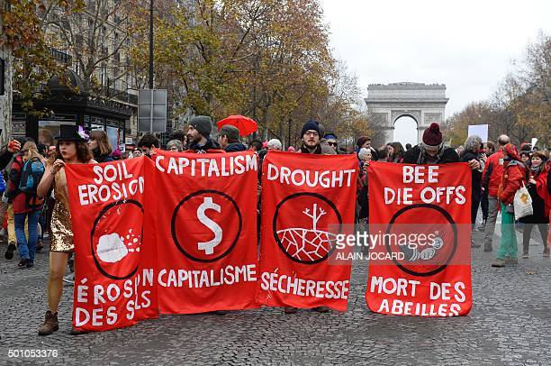 Participants hold banners reading 'Soil erosion Capitalism Drought Bee Die Offs' as activists gather for a demonstration to form a giant red line at...