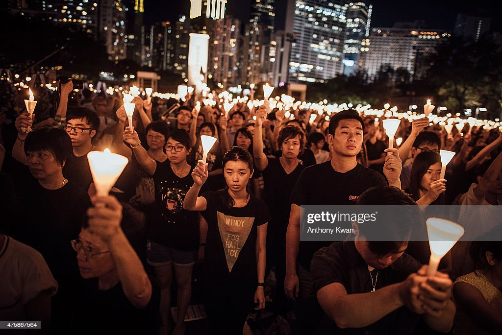 Participants hold candles and placards at Victoria Park on June 4 2015 in Causeway Bay Hong Kong Hong Kong residents held a candlelight vigil as it...