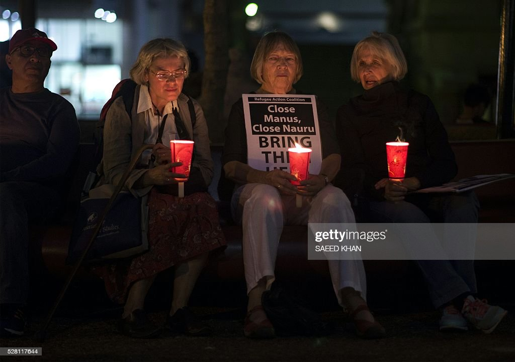 Participants hold candles during a vigil for two refugees, a Somali woman and an Iranian man who set themselves on fire on the remote Pacific island of Nauru, during a candle light vigil in Sydney on May 4, 2016. More than 750 asylum-seekers held in a Papua New Guinea detention camp launched legal action on May 4, 2016 to be moved to Australia after a court in the Pacific nation found the centre unconstitutional. / AFP / SAEED