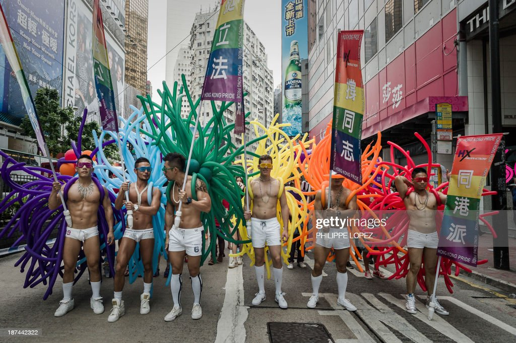 Participants hold flags during the gay pride parade in Hong Kong on November 9, 2013. Despite its reputation as an international financial hub, critics say Hong Kong remains a conservative city when it comes to gay rights, lacking protection for the sexual minority group despite having decriminalised homosexuality in 1991. AFP PHOTO / Philippe Lopez