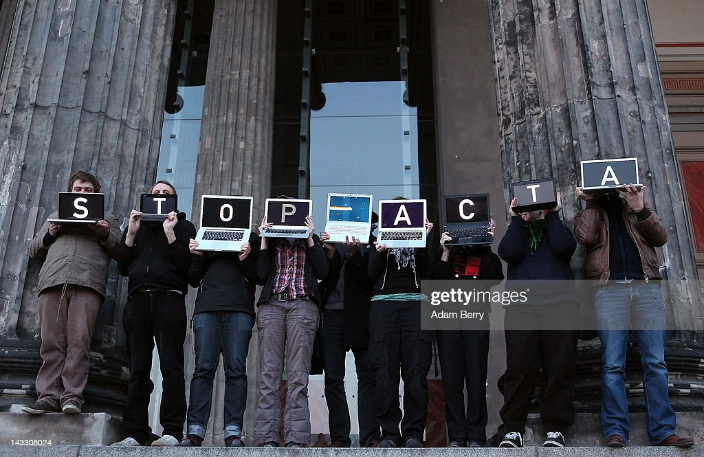 Participants hold laptop computers featuring screens with letters spelling out the words 'Stop ACTA' during a demonstration against Internet copyright restrictions resulting from the Anti-Counterfeiting Trade Agreement (ACTA) in front of the Altes Museum (Old Museum) on April 23, 2012 in Berlin, Germany. ACTA is a proposed treaty attempting to establish an international governing body with legal standards intended to protect intellectual property and prevent the production and sale of counterfeit goods. The German government has delayed a decision on the agreement, citing concerns by the Justice Ministry, and according to news reports is waiting for approval by the European Parliament prior to signing the multinational treaty.