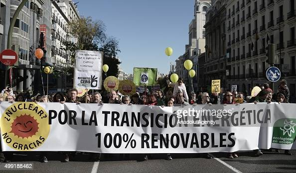 Participants hold placards and green balloons against the climate change during the 'Global Climate March' on November 29 2015 in Madrid Spain called...