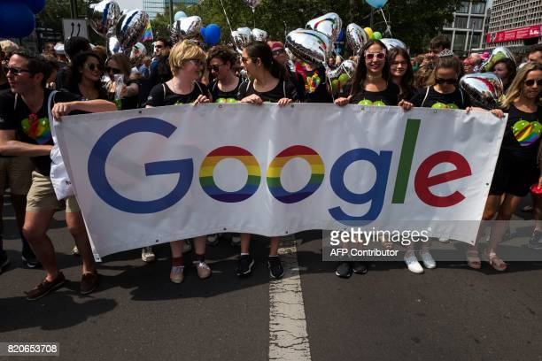 Participants hold up a Google banner during Berlin's annual Christopher Street Day gay pride parade on July 22 2017 Gays and lesbians all around the...