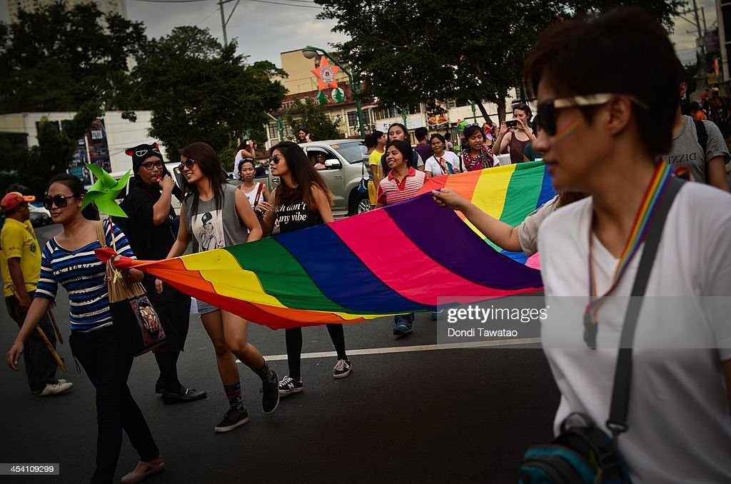 Participants hold up a rainbow banner during the Manila gay pride march on December 7, 2013 in Manila, Philippines. The march was held to celebrate the approval of anti discrimination ordnances in a handful of cities as well as the filing of the Anti Discrimination Bill before the Lower House of the Philippine legislature. The march is in its nineteenth year, making it the longest running celebration of its kind in Asia.