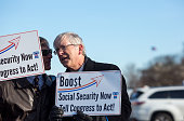 Participants hold up signs as House Democrats hold a news conference to announce the introduction of Social Security 2100 Act in front of the US...