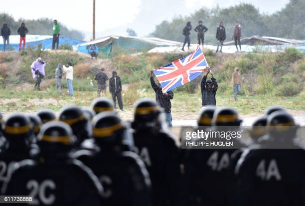 Participants hold up the Union Jack during clashes with French antiriot police during a march in support of migrants and refugees in the socalled...