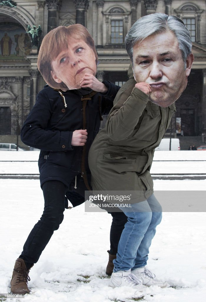 Participants in a flashmob wearing a German Chancellor Angela Merkel mask (L) and a Berlin Mayor Klaus Wowereit mask (R) dance together as flashmobbers get ready to dance the Harlem Shake in front of the Berlin cathedral February 20, 2013. The flashmob was called in an effort to gather as many people as possible and perform the Harlem Shake in sub-zero temperatures. AFP PHOTO / JOHN MACDOUGALL