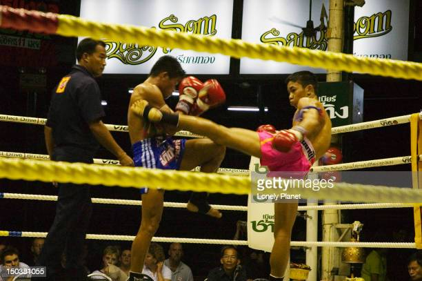 Participants in action during Thai kickboxing match.