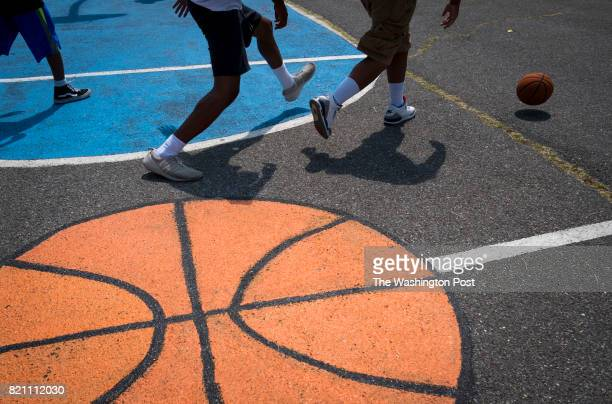 Participants in 'Camp on the Go' play basketball on the West Elementary School campus on July 20 2017 in Washington DC The camp's goal is to keep...