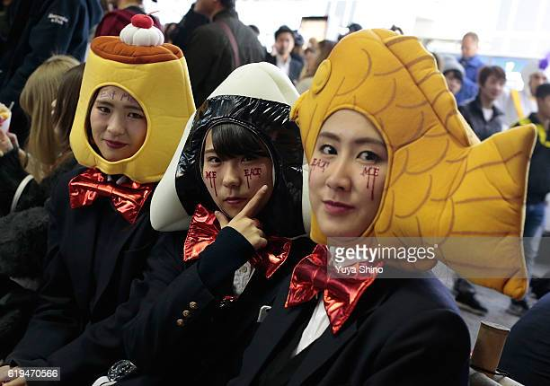 Participants in costume of Pudding Rice ball and A fishshaped pancake filled with bean jam pose for a photograph during Halloween celebrations at...