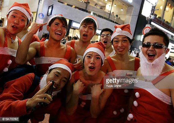 Participants in costume of Santa Claus pose for a photograph during Halloween celebrations at Shibuya district on October 31 2016 in Tokyo Japan