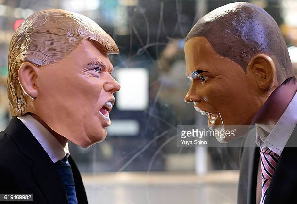 Participants in costume of US President Barack Obama and Republican presidential nominee Donald Trump pose to look at each other for a photograph...