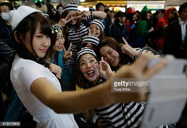 Participants in costume pose for a selfie photo during Halloween celebration at Shibuya district on October 31 2016 in Tokyo Japan