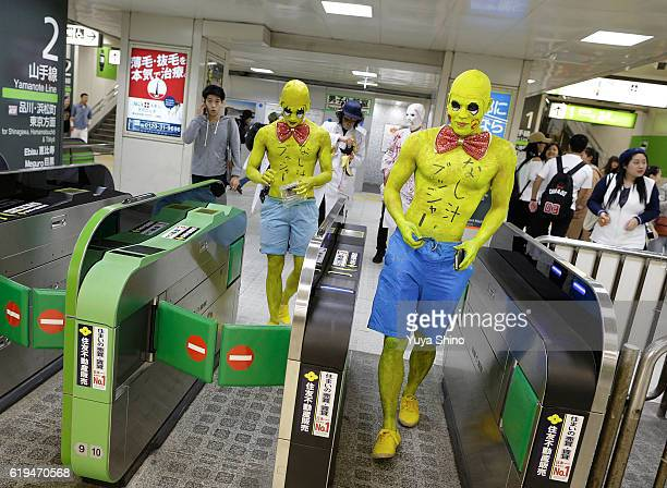 Participants in costume walk past a gate of a train station as they participate in Halloween celebration at Shibuya district on October 31 2016 in...
