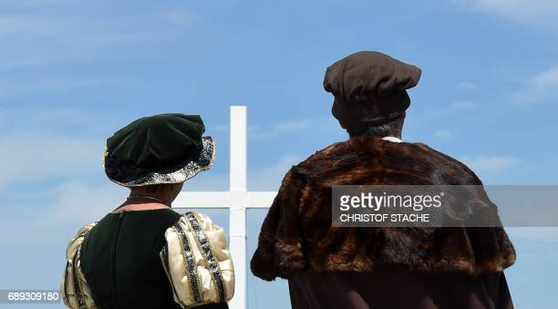 Participants in historical clothes stand in front of a big crucifix during the final mass of the Kirchentag festival celebrating the 500th...