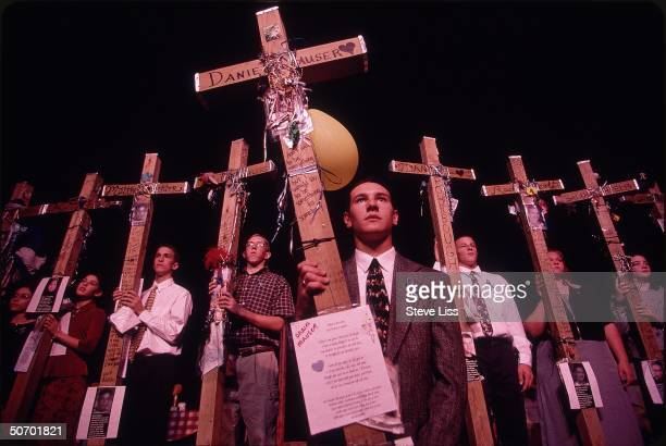 Participants in memorial for Cassie Bernall carrying 13 crosses in memory of Cassie 12 other victims of last April's massacre at Columbine High...