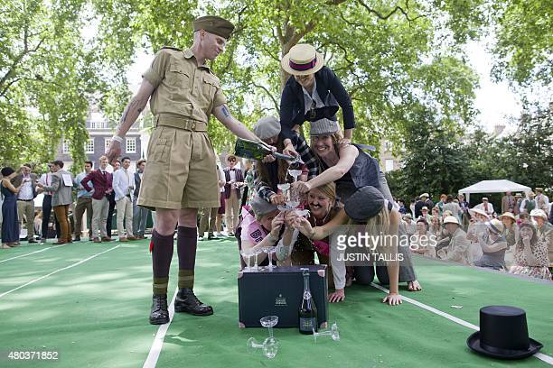 Participants in period costumes take part in the Champagne Charlie Pyramid of Dextrous Dandies competition during 'The Chap Olympiad' in central...